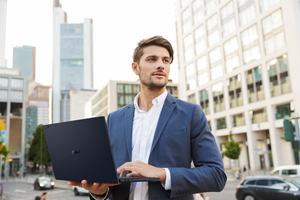 Picture of a serious handsome young business man standing near business center using laptop computer.; Shutterstock ID 1445094773; purchase_order: -; job: -; client: -; other: -