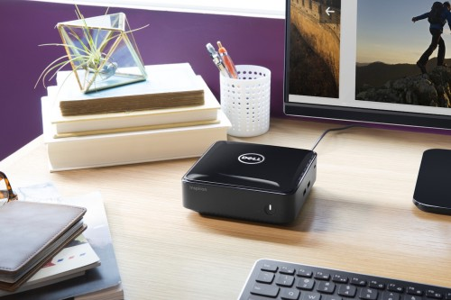 Close up image of a Dell Inspiron Micro Desktop (Model 3050) on a desk in a home office with Dell 23-inch S2340L monitor and KM714 wireless keyboard (Tangerine). Micro Desktop is shown on next to a small stack of books.